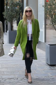 Elle Fanning in a green Topshop coat, white Christopher Kane blouse, distressed jeans, Miu Miu Madras bag, Miu Miu sunglasses and Miu Miu Donna jeweled pumps in the Rue du Faubourg Saint-Honoré at Paris Fashion Week.