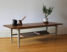 A stylish long sleek coffee table with tapered legs and magazine shelf below, made in solid afromosia hardwood (African teak). Richard Hornby furniture was made to a high quality and originally sold by Fyne Ladye furniture of Bath, Heals and other high end designer furniture shops during the 1950s and 1960s. The table came to me with the legs treated with grey chalk paint. The top and magazine shelf have been sanded and finished with natural waxes and buffed. DIMENSIONS Approximately 42cm…