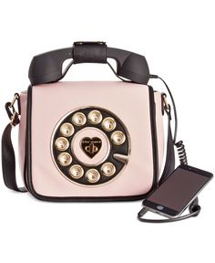 "Betsey Johnson Phone Crossbody. Call me definitely. This fun crossbody bag from Betsey Johnson features a retro phone headset that plugs into any cellphone. Faux leather Top handle with 2"" drop; detachable strap with 23"" drop Fold-over flap with turn-lock closure Exterior features gold-tone hardware Interior features 1 zip pocket and 2 slip pockets Removable, functional phone set handle can be used as a listening device when plugged into your cellphone 10-1/2"" W x 4-1/2"" H x 7"" D"