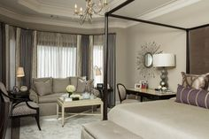 The master bedroom features a cozy sitting area by the bay window and a bedside desk that is both practical and stylish.