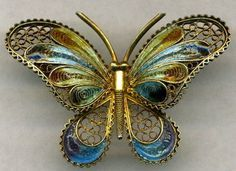 """""""FRENCH ART NOUVEAU BROOCH features Plique-a-Jour, the most desired of all enameling techniques. The enameling is in blues, yellow-green, purple and rusty-oranges, a popular palette of the day. When held to the light, the enameling looks like stained glass, which is the intention of the technique. The brooch has intricate filigree detail that was all done by hand. The entire brooch measures about 1 7/8"""" wide by about 1 ¼"""" long"""