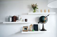 This is a good example of how you may style your shelves in a living room or dining room. We styled with books, glitter jars, candles, and a globe I got at the flea market. Vary the size and spacing of your shelf accessories to create a styled look. Fresh flowers always look good, I like them in a simple kitchen jar. A row of 3 candles gives a serene repetition. Try to style with a mix of solo items and a repetition of items for variety and visual interest.