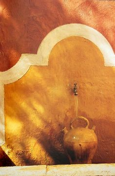 Stucco wall with burnt orange, cream and rust design framing fountain/spigot --- Provence Style of Living: Jerome Coignard
