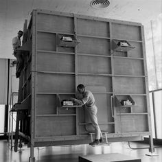 "Ken Isaacs (front) and a colleague work on the outside of Isaccs' ""knowledge box,"" Chicago, 1962"