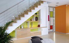 Le vert du fond de la bibliothèque installée sous les escaliers est assorti à celui de la porte décorée d'une Impression cubisme inspirée de...