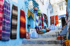 Discovering Chefchaouen the Blue City of Morocco. Colorful Rugs on display in the streets. Explore Morocco with Oasis Overland. http://www.oasisoverland.co.uk/trips/morocco/list/