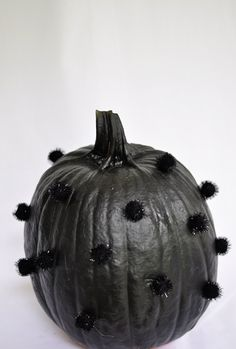 To give the illusion of a textured polka-dot pumpkin we applied craft poms in the same color of the pumpkin using small dots of glue.