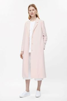 This long coat is made from a cotton-mix with a silky lining and side slits. Slightly oversized, it has wide notched lapels, long sleeves and in-seam pockets. It is completed with hidden tonal buttons.