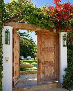 Weathered double doors lit by outdoor wall lanterns open to the lush garden and in ground pool. Weathered double doors lit by outdoor wall lanterns open to the lush garden and in ground pool. Traditional Home Exteriors, Traditional House, Outdoor Wall Lantern, Outdoor Walls, Outdoor Decor, Gate Design, House Design, Wooden Double Doors, Double Door Design