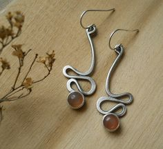 I made these squiggly peach/ blush colored, red moonstone earrings by hand, in sterling silver. I sanded them and wire brushed them to a soft