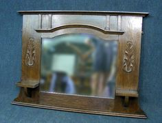 A lovely oak Arts and Crafts carved  over mantle mirror   Solid oak frame  Original bevel edged mirror  Lovely carved foliate side decoration with small shelves below  Measures approx   75 cms High   107 cms Wide   13 cms Deep