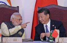 Indian Prime Minister Narendra Modi, pointing, talks with Chinese President Xi Jinping on Sunday during...