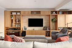 Decoração de apartamento integrado e com crianças. Sofá de madeira estofado com almofadas em cores, obras de arte, jardim vertical e tapete, poltrona cinza, luminária de chão e estante com nichos de madeira.