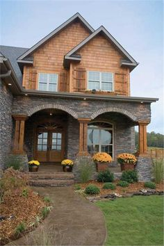 Two sets of matching flower pots frame the covered entrance of this two-story Craftsman style home. The wood door with glass panes under the arched entryway opens to the foyer and Great Room.