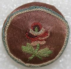 18th century embroidered silk men's waistcoat button. Border has chain stitch embroidery and center is embroidered with a single flower.