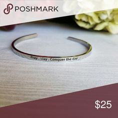 """STAINLESS STEEL BRACELET Inscribed with a meaningful message, this cuff can help you get through your day. Featuring the saying """"Pray-Slay-Conquer the day"""". Cuff slides on easily and can be adjusted to fit your wrist comfortably.  - 3mmW - Stainless Steel - Made in the USA Jewelry Bracelets"""