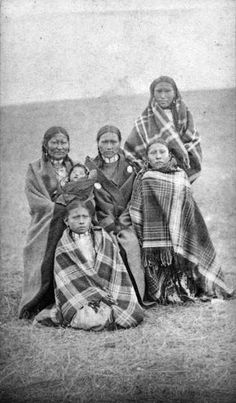 Spotted Tails wife and family, Native American (Sioux) woman, boys, girls, and baby pose outdoors, possibly at Pine Ridge Agency, South Dakota. Each person is wrapped in a blanket. The boys wear hair pipe chokers.[Cross, W. R. (William R.)between 1875 and 1885].