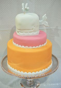 Whale Baby shower cake for CoCo and her expecting baby Penelope. Carved whale cake, covered in light blue fondant with two tiers of brightly coloured, orange and pink fondant covered cake.