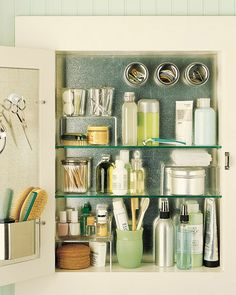 Organization idea from Martha Stewart.  Have galvanized metal cut to fit the back of the medicine cabinet and inside the door. Adhere metal with caulk. Attach magnetized hooks, a notepad holder for brushes and combs, and spice canisters for hair elastics and barrettes.