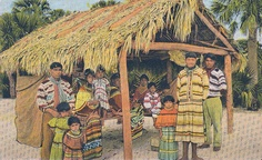 This postcard from 1948 shows a group of Seminole people in front of a  typical thatched house in the everglades of South Florida