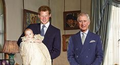 Official photo of baby Prince George, held by his uncle, Prince a Harry, with his grandfather, Prince Charles, looking on.