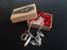 This Gothic Vampire inspired necklace comes with a red glass bead, letter v, silver vampire fangs, silver hanging bat and silver bullet. A great necklace