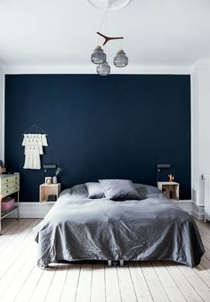 Nordic bedroom with a dark blue colored end wall and grey pillows and bedspread.