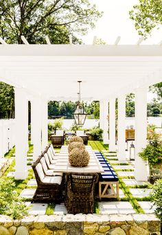 Patio dining space with a white pergola and a brass lighting fixture