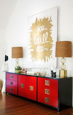 Credenza in entryway with matching lamps and gold metallic art