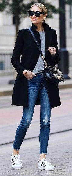 #spring #outfits woman in gray shirt under black coat wearing blue jeans and Adidas Superstar shoes. Pic by @vogue__cafe