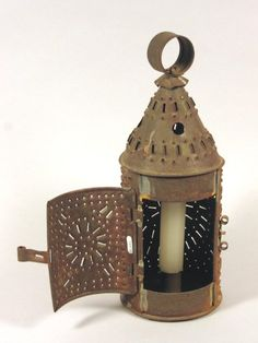Image of T94-8, Pierced tin lantern with pointed top with round circle to carry it by at top. Candle holder inside. MHS Museum Collections