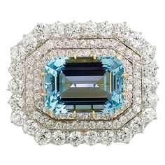 Very fine and rare Victorian era brooch by Tiffany & Co., circa 1890s. It centers upon a 19 carat emerald cut aquamarine of exceptional quality and color, and is flanked by three rows of very high grade European cut round white diamonds of approx. 7.5 - 8.0 cts. Brooch is set in both platinum and 18K yellow gold; it also features a brooch clip fitting, as well as a bail so that it could be worn as a pendant. Hallmarks: Tiffany & Co.