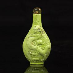 Piasa - CHINE - XIXe siècle  Flacon tabatière en porcelaine moulée émaillée verte d'un dragon à la recherche de la perle sacrée sur une face, d'un tigre et de bambous sur l'autre face. Marque Yongzheng.  Bouchon en quartz.