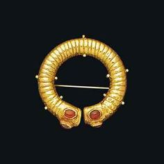 A SASANIAN GOLD HAIR- OR EARRING  CIRCA 3RD-6TH CENTURY A.D.  The hollow corrogated penannular ring with flat terminal collars, each with three oval box-settings with cabochon garnets, on later brooch mounting