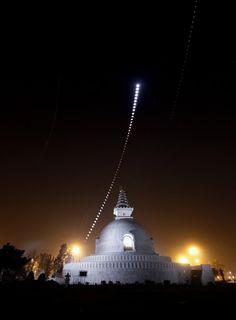a lunar eclipse over an indian peace pagoda, by chander devgun