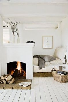 Cozy neutral bedroom with built-in fireplace, white-washed floors and natural fiber accents.