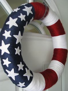 "American Flag Yarn Wreath - I used a 14"" straw wreath (keep the plastic wrap on, that way there isn't a mess!), Caron Simply Soft in Autumn Red, White and Country Blue.  I bought the adhesive-backed felt sparkle stars from Michael's."