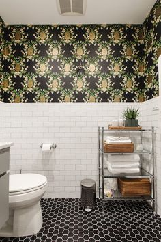 The walls received a gorgeous treatment of white subway tile with gray grout and an unexpected yet bold touch – black wallpaper featuring golden pineapples from Rifle Paper Co.
