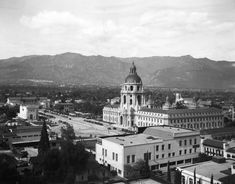 (1930)* - Scenic view of Pasadena City Hall and its surrounding area, with mountains in the background. City hall is located at 100 North Garfield Avenue in Pasadena. Building on left of photo (past the tall pine tree) is the Y.W.C.A., located on the southeast corner of Marengo Avenue and Holly Street. It is a 3 story, plain, boxy building with long horizontal windows. Date built: 1920-1922. Designed by Julian Morgan in Mediterranean style.	  Water and Power Associates