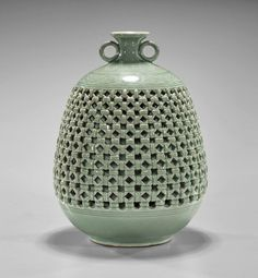 Korean celadon glazed porcelain jar; of oval form with small mouth and two loop handles, reticulated basket weave design to body and interior cylindrical bottle; signed; H: 9 1/2""