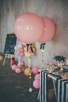 Pink and gold wedding decor: Modern weddings often use alternative decor elements, such as balloons, to fill the space in giant loft venues. These bubblegum pink geronimo balloons tied down with gold garland are a lighthearted detail to add next to welcome tables or food stations.