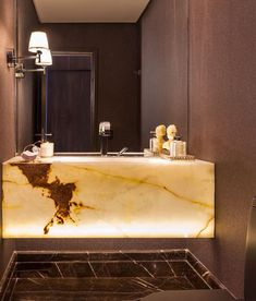 This high-end bathroom vanity uses backlit onyx to create a statement. Notice how the surrounding walls have a simple style to not overwhelm the interior design.