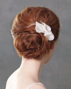 Relaxed updos become a touch more formal, and far more secure, when anchored with refined combs, like this organza-flower-and-feather one #weddinghair