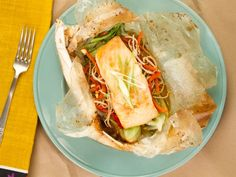 Baking salmon in parchment paper with just a couple tablespoons of an Asian-style marinade and crispy vegetables renders the fish extremely flavorful and moist.