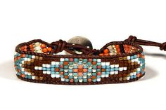 Coral Blue Turquoise Sky Eye loom leather wrap bracelet Bead loom leather wrap bracelet featuring sky eye design in coral and blue turquoise with gold and white on naturally dyed golden brown leather from the USA. These are 11/0 Japanese seed beads. The button is open round antique