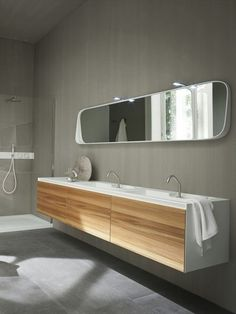 Wall-mounted Corian® washbasin unit with doors, design by Giulio Gianturco (2012)