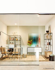 Office with glass doors, beige walls, wood chairs, brown rug, colorful artwork, silver bookshelves, and flowers