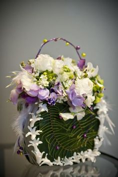 Flower purse with hyacinth blossoms, ferns, feathers, sweetpeas, kalanchoe, jasmine and berzillia. Created by Françoise Weeks.