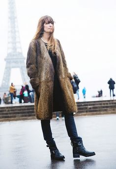Caroline de Maigret wears a brown fur coat over black basics and finishes the look with motorcycle boots