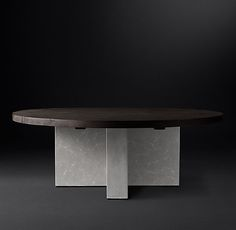 RH Modern's Concrete Pier Round Dining Table:Postmodern design on a substantial scale, our collection by Ed Robinson and Thomas Bina offers an unexpected contrast of texture and form. Spare of line and commanding in presence, the table's thick planks of reclaimed French oak are supported by weighty concrete slabs.